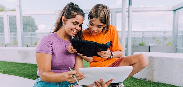 A young girl and boy smile looking at an Ipad.